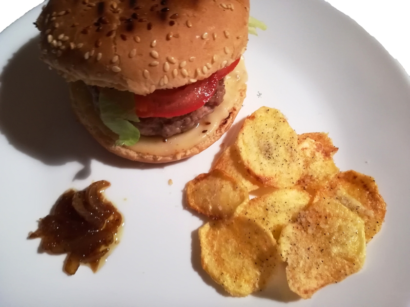 Hamburger con cipolla caramellata, accompagnato da chips cacio e pepe