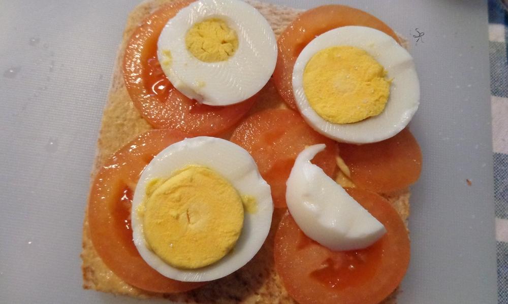 Preparazione club sandwich con avocado, pomodoro, uovo, senape, origano e limone