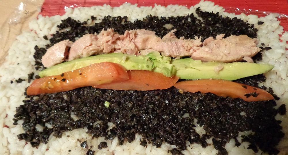 Composizione del roll con olive nere, tonno, avocado e pomodoro